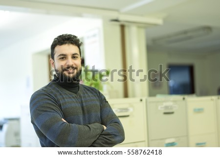 Office worker posing in office looking at camera with ambient light