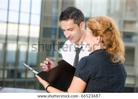 Office worker sign documents outdoor - stock photo