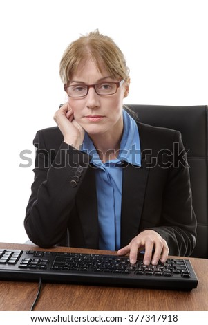 Office worker sits at her desk not looking happy - stock photo