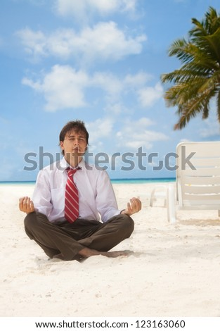 Office worker sitting on the beach an meditating - stock photo