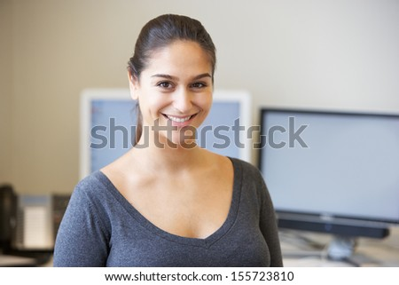 Office Worker Standing In Front Of Computers - stock photo