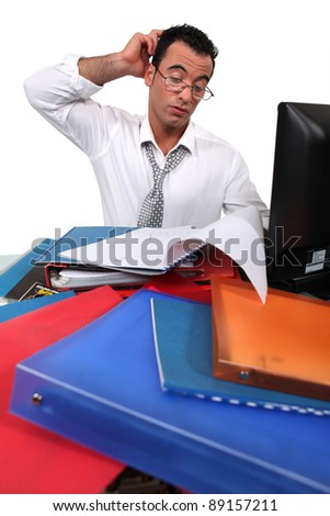 Office worker surrounded by paperwork - stock photo