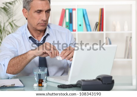 Office worker taking medication for headache - stock photo