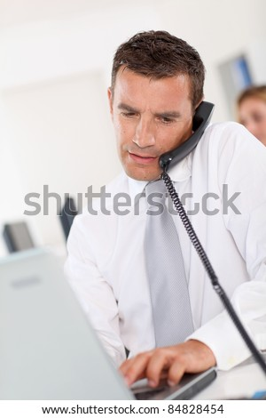 Office worker talking on the phone in office - stock photo