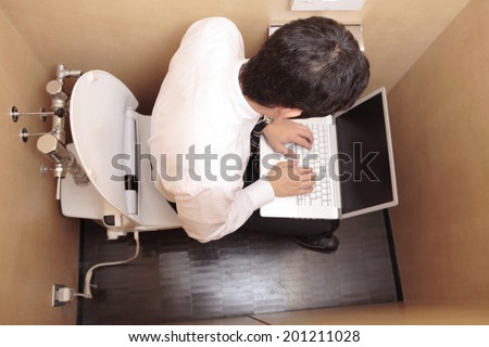Office worker to computer in the toilet - stock photo
