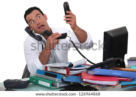 Office worker trying to answer multiple phones - stock photo