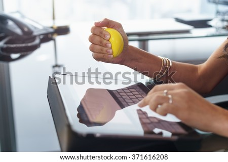 Office worker typing email on tablet computer. The woman feels stressed and nervous, holds an antistress yellow ball in her hand - stock photo