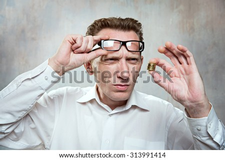 Office worker up his eyeglasses and look for a coins extremely surprise. Small salary concept.  - stock photo