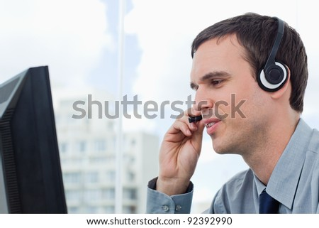 Office worker using a headset in his office - stock photo