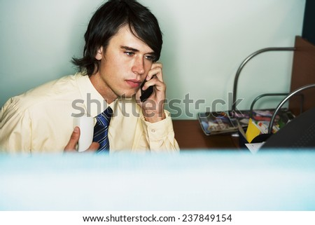 Office Worker Using Cell Phone and Land Line - stock photo