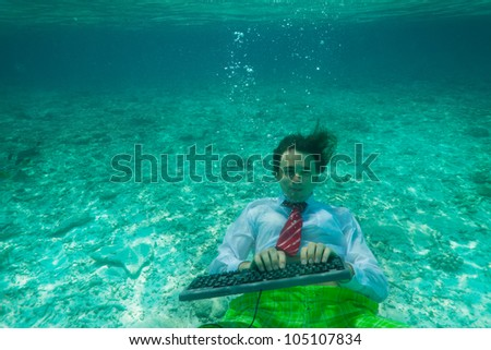 Office worker wearing formal clothes with keyboard underwater - stock photo