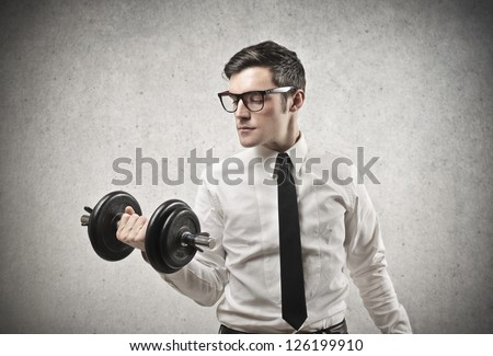 Office worker with glasses raising a dumbbell - stock photo