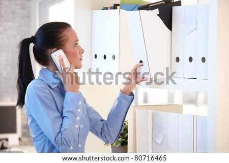 Office worker woman talking on mobile phone while choosing file folder from shelf.? - stock photo
