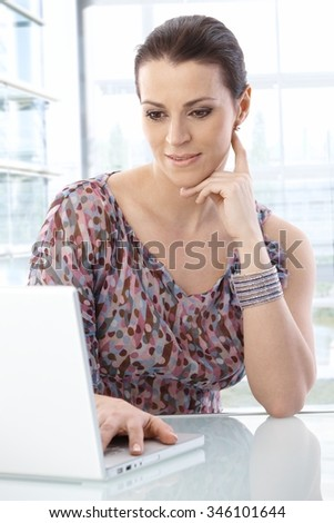 Office worker woman using laptop computer at desk, looking at screen, smiling. - stock photo