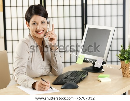 Office worker working at desk in office, talking on phone, taking notes. Copyspace on screen.?