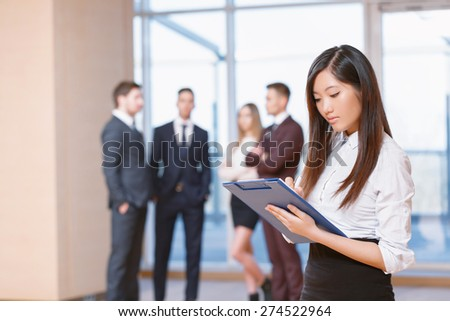 Office workers.  Asian young business woman standing in foreground looking at the tablet seriously, her co-workers discussing business matters in the background - stock photo