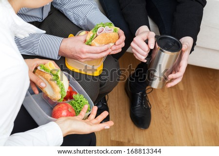 Office workers have a break from work to eat second breakfast - stock photo