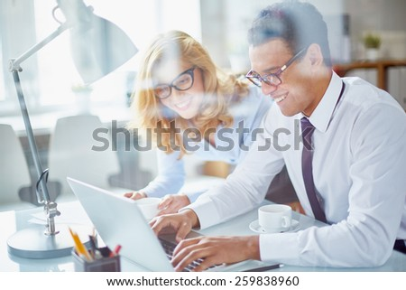 Office workers looking at laptop and smiling