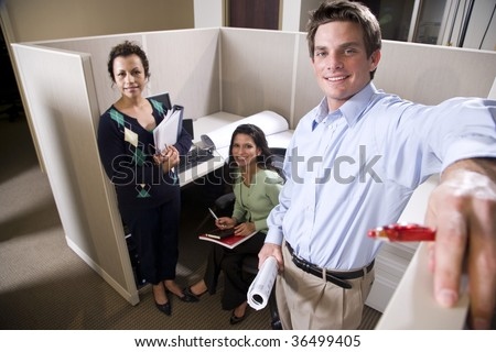 Office workers meeting in a cubicle - stock photo