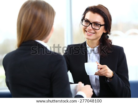 Office workers on coffee break, woman enjoying chatting to colleagues, smiling. - stock photo