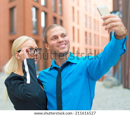 Office workers taking selfie with cellphone.