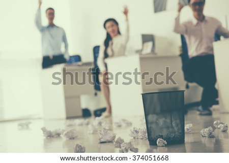 Office workers throwing crumpled paper balls in the basket