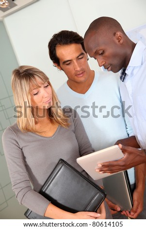 Office workers using electronic tablet in office - stock photo