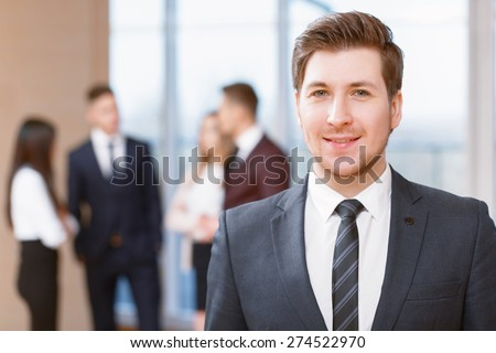 Office workers.  Young business man standing in foreground smiling, his co-workers discussing business matters in the background - stock photo