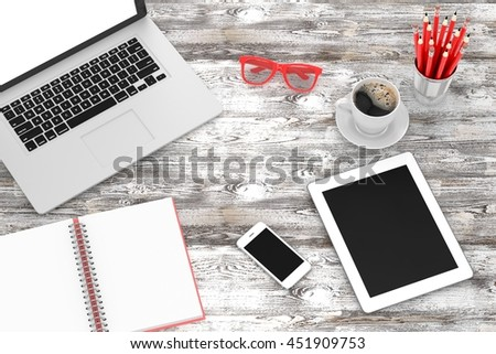 Office workplace set on wooden grey table. Pc, tablet, smartphone, notebook, red stationery, red glasses, red cup of coffee.