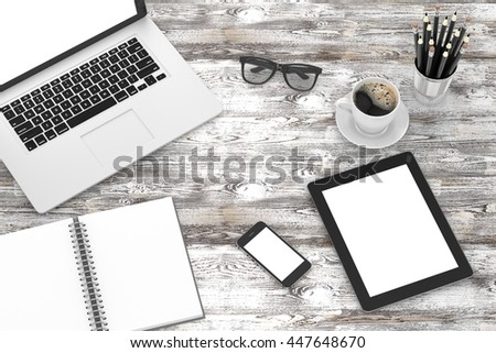 Office workplace set on wooden grey table. Pc, tablet, smartphone, notebook, stationery, glasses, cup of coffee. - stock photo