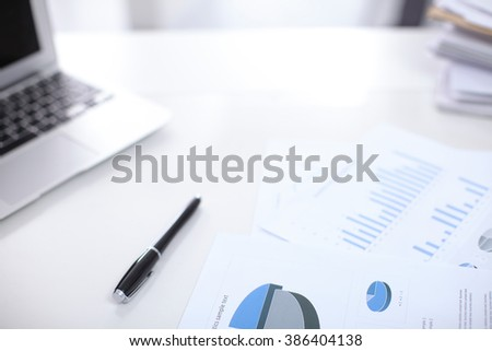 Office workplace with a laptop and contract document on the light reflecting table