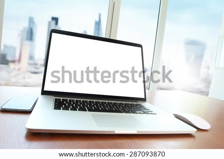 Office workplace with blank screen laptop and smart phone on wood table - stock photo