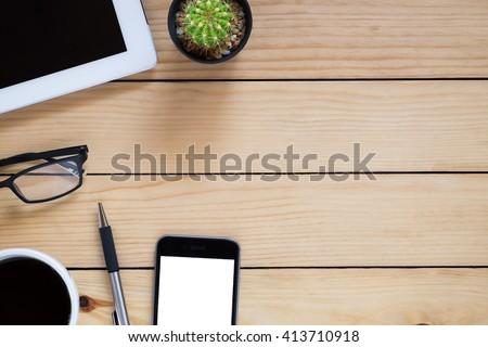 Office workplace with blank screen tablet, smartphone, pen and coffee cup on rustic wood table.Top view with copy space - stock photo