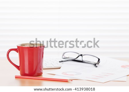 Office workplace with coffee and charts on wooden desk table in front of window with blinds - stock photo