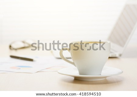 Office workplace with coffee cup, laptop and supplies on wood desk table in front of window with blinds. View with copy space