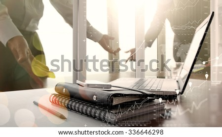 Office workplace with digital business diagram laptop and smart phone on wood table and two colleagues discussing data in the background - stock photo