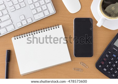 office workplace with keyboard, notepad, mouse, smartphont and coffee of cup on wooden table. over light