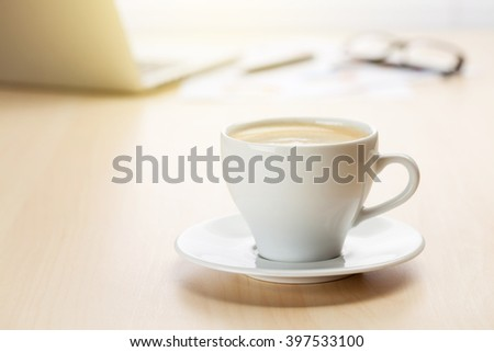 Office workplace with laptop and coffee on wooden desk table in front of window. Sunset light. Focus on cup - stock photo