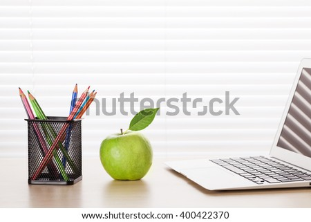 Office workplace with laptop, apple and pencils on desk table in front of window with blinds - stock photo