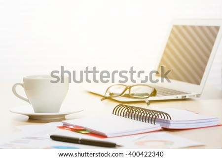 Office workplace with laptop, coffee cup, reports and notepad on desk table in front of window with blinds. Sunset light - stock photo