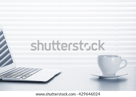 Office workplace with with laptop and coffee cup on wooden desk table in front of window with blinds. Toned. View with copy space - stock photo