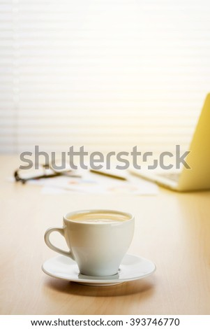 Office workplace with with laptop and coffee on wooden desk table in front of window with blinds. Sunset light. Focus on cup - stock photo