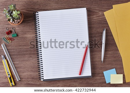 Office Workspace. Top View of a Business Workplace. Wooden Desk Table, Paper Cutter, Ruler, Pen, Pencil, a Blank Notebook, Envelope, Red Pen, Plant Pot, Clips. Copy space for text or Image - stock photo