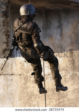 Officer in full tactical gear with weapons climbing down a rope. - stock photo