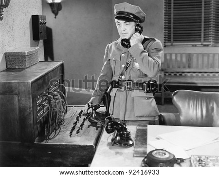 Officer talking on a telephone next to a switchboard - stock photo