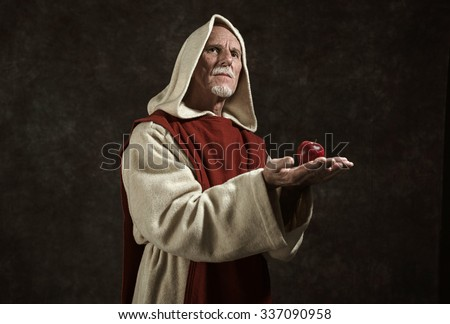 Official portrait of monk holding apple. Studio shot against dark wall. - stock photo