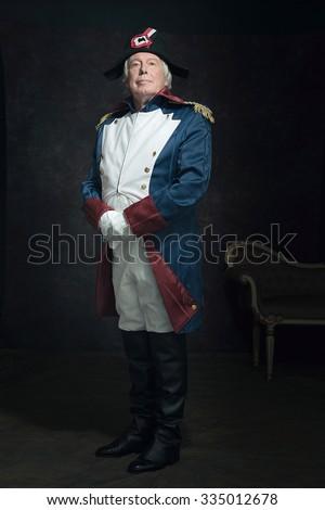 Official portrait of senior man dressed in historical emperor costume. Studio shot against dark wall. - stock photo
