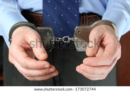 Official's hands in handcuffs - stock photo