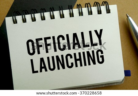 Officially launching memo written on a notebook with pen - stock photo
