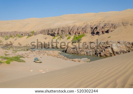 Offroad camping at Kunene River in front of towering ancient Namib Desert sand dunes of Namibia and Angola